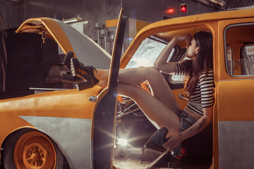 Woman mechanic with screwdriver in sexy shirts is sitting on the