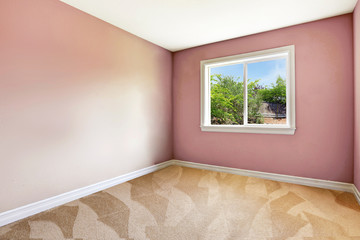 Bright empty room with one window, carpet floor and pink walls