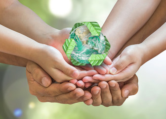 Parent guardian children hands holding together recycled green leaf arrow sign planet on blur nature greenery background sun flare Environment CSR ESG concept Element of this image furnished by NASA