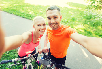 couple with bicycle taking selfie outdoors