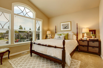 Cozy Beige bedroom with vaulted ceiling and elegant Victorian style bed.