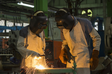 workers with protective mask welding metal