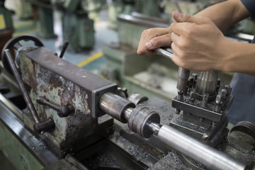 hands are setting up with machine.Setting up a steel lathe machine.