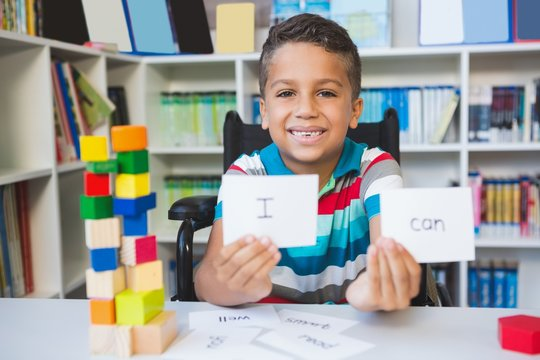 Disabled boy showing placard that reads I Can in library