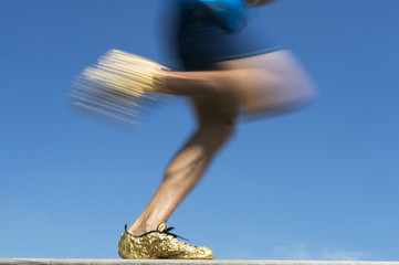 Athlete wearing gold running shoes runs past in a blur against bright blue sky