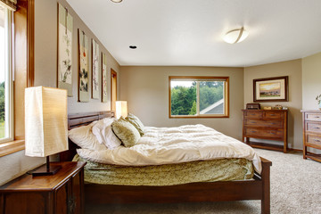 Cozy bathroom interior with double wooden bed and carpet floor.