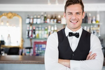 Portrait of waiter standing at bar counter