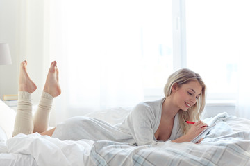 happy young woman with notebook in bed at home