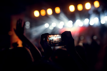 Photographing a live act at a concert with a smart phone.