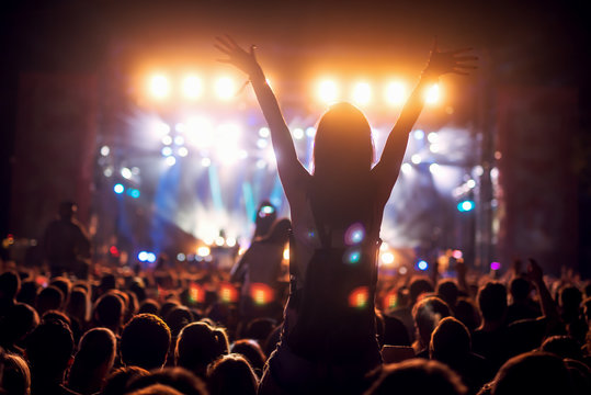 Silhouette of a girl at a concert holding her hand up and having fun.