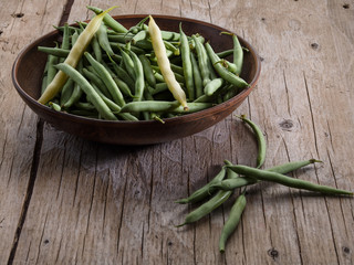 bean pods are green in pottery on a wooden table