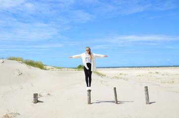 junge Frau am Meer balanciert auf einem Holzpfahl