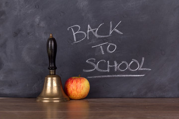 Old fashioned bell and apple against a blackboard