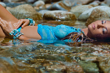attractive boho woman lying in water on stone beach