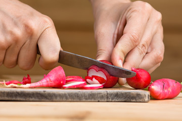 hands slicing radishes on the cutting board