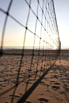 Netz eines Beachvolleyballfeldes bei Sonnenuntergang