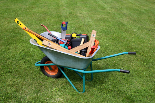 Wheelbarrow with construction tools on green grass