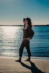 Femme en contre jour au soleil levant, sur la plage des Saintes-Maries-de-la-Mer