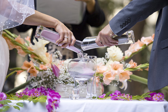 Sand ceremony vase in a wedding with colored sand being mixed together