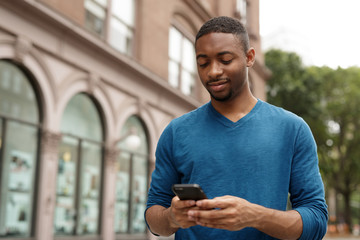 Young man in city texting cell phone