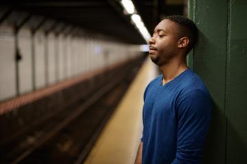 Young man in city at subway platform tired