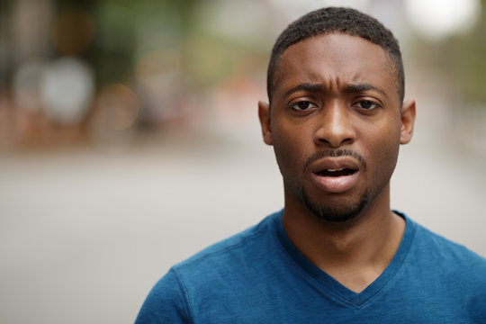 Young black man in city shocked face portrait