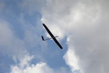 RC glider silhouette flying in the blue sky, white clouds background