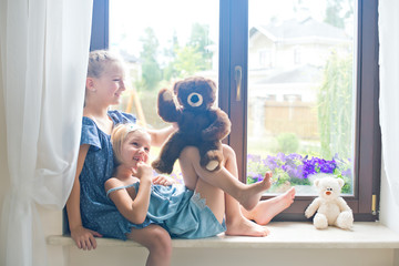 Two cute european toddler girls sitting near window at home playing teddy bears