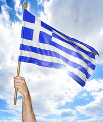 Person's hand holding the Greek national flag and waving it in the sky, 3D rendering
