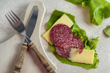 Breakfast with salami, cheese and salad on rustic background