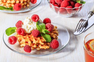 Waffles garnished with mascarpone and raspberries.