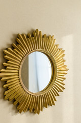 Beautiful modern golden mirror in shape of sun on the wall at home for decoration close-up, copy space for text.