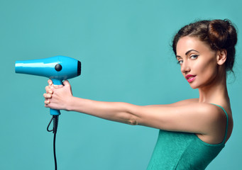 Happy young curly brunette woman with hair dryer on blue mint ba