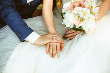 Hands of the bride and groom with rings  wedding bouquet.