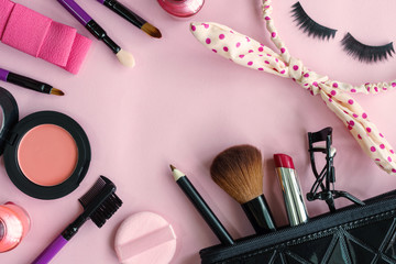 various makeup products and cosmetics isolated on pink