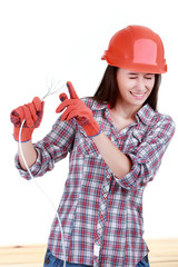 Portrait of young female builder in helmet with cabel on white