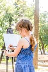 young happy child girl drawing a picture outdoors, kid painting