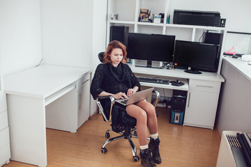 Young business woman with a computer in the office