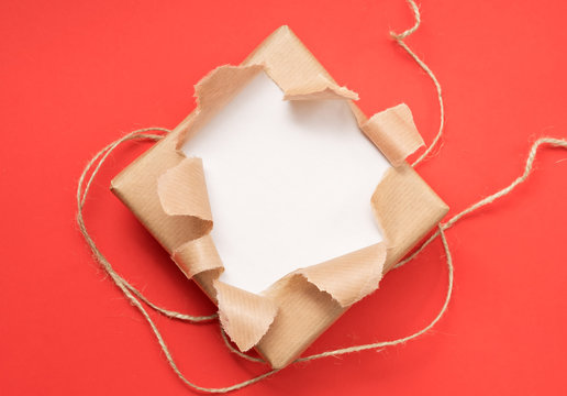 kraft torn paper. gift on red background