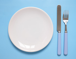 An empty white dinner plate, knife and fork on a blue background, arranged as a place setting
