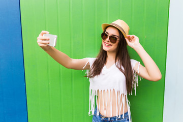 Hipster cool girl taking picture on smartphone self-portrait, screen view