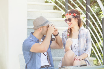 Happy young couple enjoying their summer vacation. They are sitting on the outdoor steps while young man is taking photo of his beautiful girlfriend.