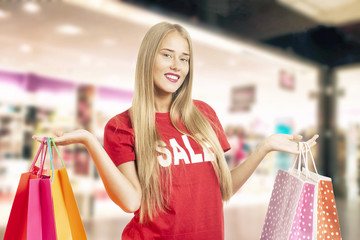 Portrait Of Young Woman Wearing a Red Sale T-shirt Holding Shopping Bag on a Shopping Centre