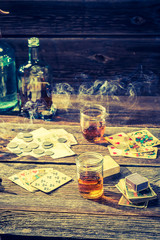 Vodka, cigarettes and cards on old table for illegal poker