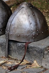 Conical or norman casque steel medieval helmet placed on curbside