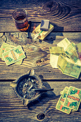 Vodka, cigarettes and cards on vintage illegal gambling table
