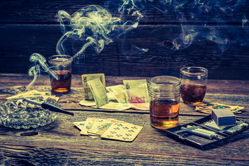 Vodka, cigarettes and cards on old illegal gambling table