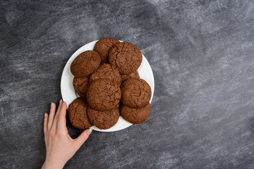 Picture of hands holding chocolate cookies over wooden background