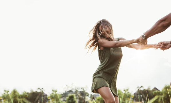Attractive woman dancing in the field with her boyfriend