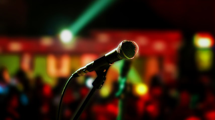 Microphone on stage ready for performer with full audience blurred background